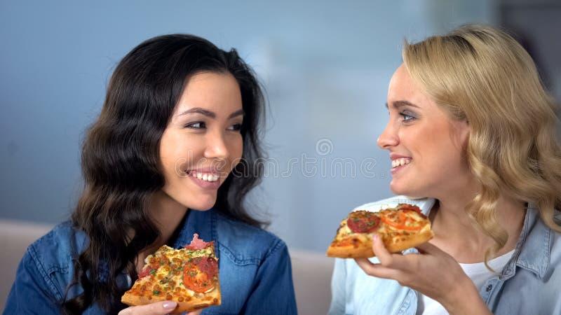 Donne sorridenti che spendono insieme tempo, mangiando pizza a casa, consegna dell'alimento fotografia stock