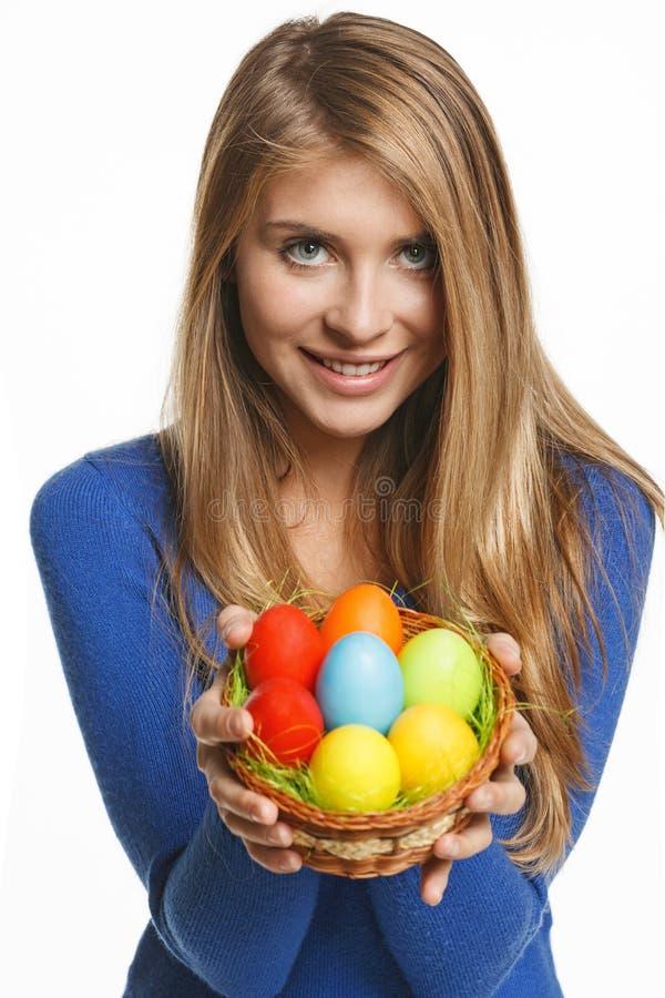 Canestro sorridente della tenuta della donna con le uova di Pasqua immagine stock libera da diritti