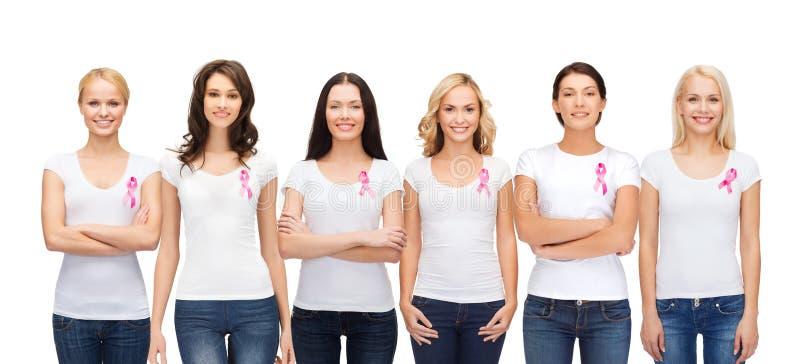 Donne sorridenti con i nastri rosa di consapevolezza del cancro fotografia stock libera da diritti