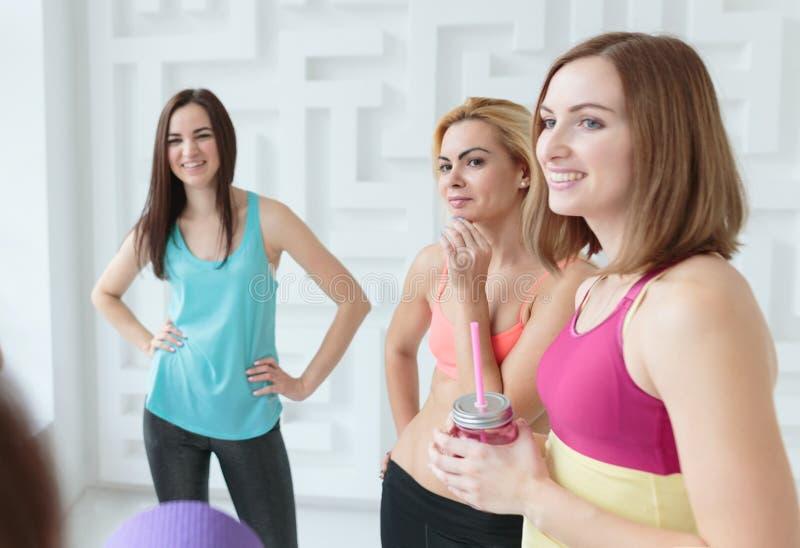Donne sorridenti felici che chiacchierano dopo il loro allenamento nello studio di forma fisica immagine stock