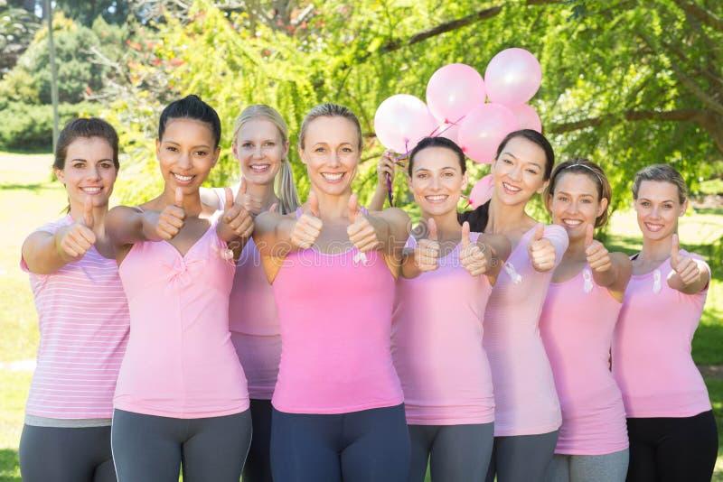 Donne sorridenti nel rosa per consapevolezza del cancro al seno fotografie stock libere da diritti