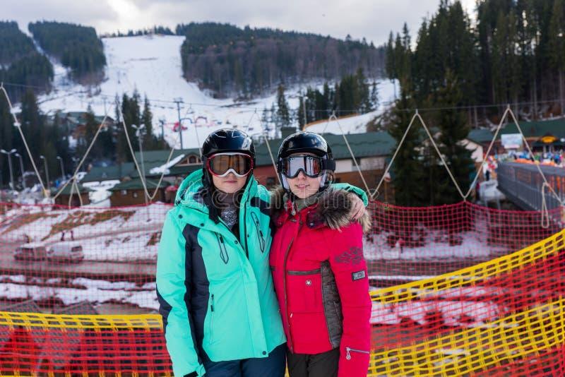Donne sorridenti in vestiti di sci, con i caschi e l'interim degli occhiali di protezione dello sci immagini stock libere da diritti