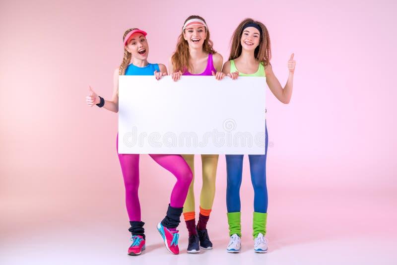 Donne sportive allegre che tengono insegna in bianco immagini stock libere da diritti