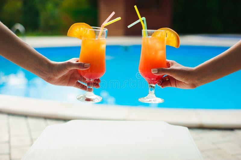 Donne in stagno che si rilassa con il succo, giovani belle ragazze sexy del bikini che riposano nella vacanza sulla stagione esti fotografia stock