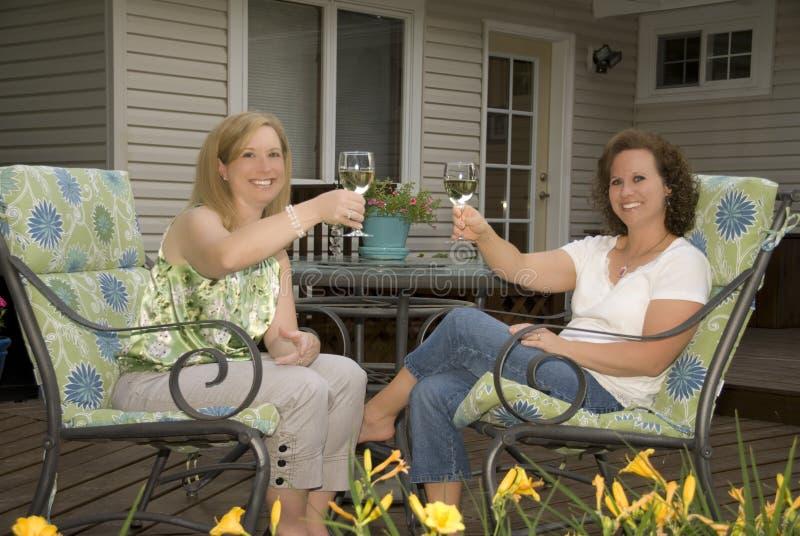 Donne sul patio che tostano i vetri di vino immagine stock libera da diritti