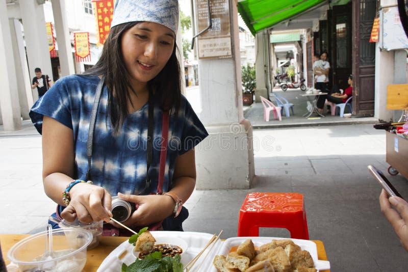Donne tailandesi del viaggiatore che mangiano l'alimento cinese Fried Tofu della via con le verdure e la salsa dolce al ristorant immagine stock