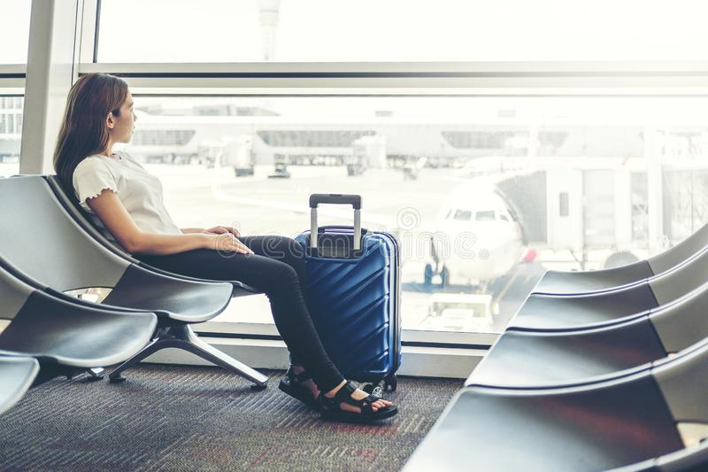 Donne turistiche che per mezzo del telefono all'imbarco aspettante dell'aeroporto internazionale immagini stock