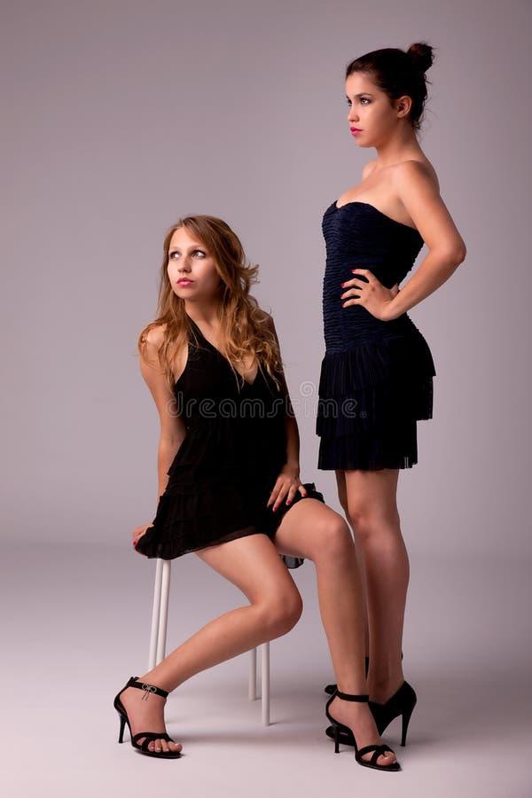 Donne, una che si siede su un banco l'altra condizione fotografia stock libera da diritti