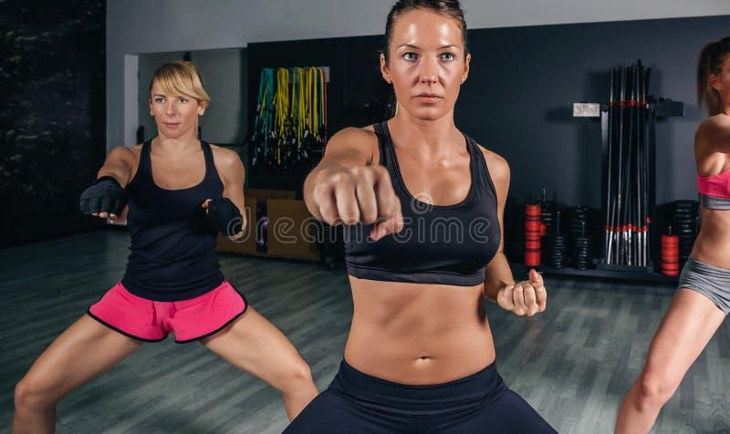Donne in una perforazione di addestramento della classe di pugilato immagine stock