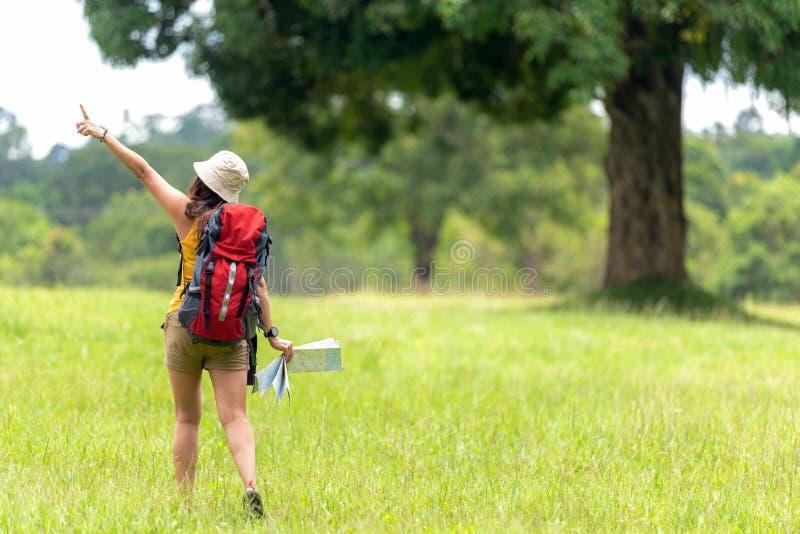 Donne viandante o viaggiatore con la mappa della tenuta di avventura dello zaino per trovare le direzioni e camminata per rilassa fotografie stock libere da diritti