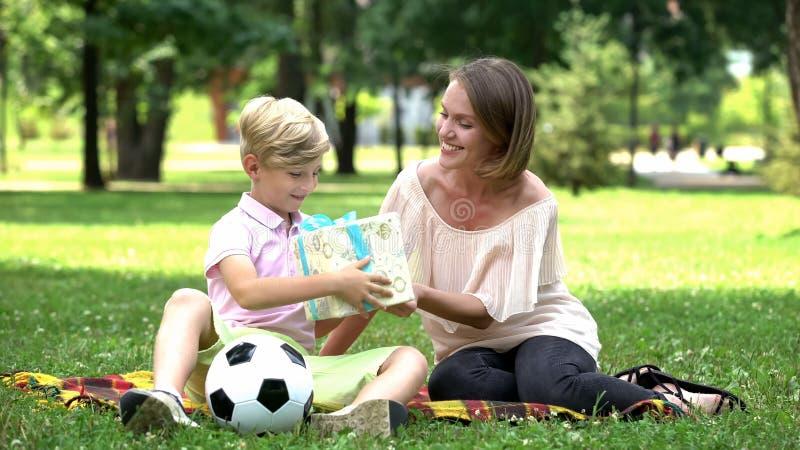 Donner affectueux de mère actuel au fils sur l'anniversaire, incorporation de rêve d'enfant photographie stock libre de droits