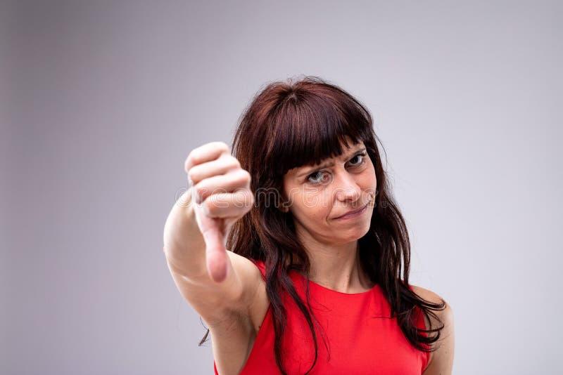 Donner attrayant de femme des pouces font des gestes vers le bas photo stock
