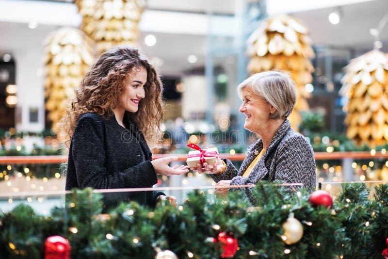 Donner d'adolescente actuel à la grand-mère au centre commercial à Noël image libre de droits