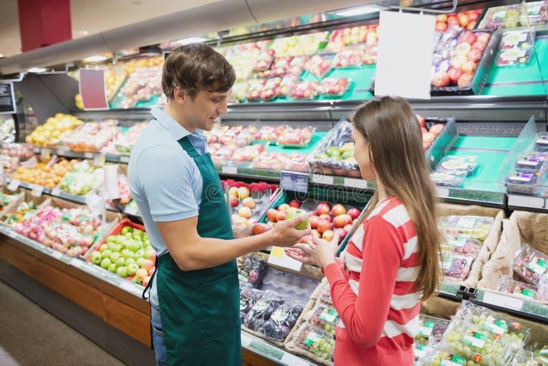 Donner d'employé de magasin conseille à un client images libres de droits