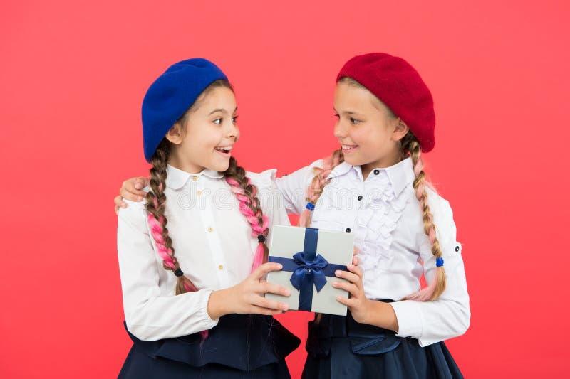 Donner le cadeau pour vous Petit enfant mignon donnant un présent à l'ami sur le fond rose La petite fille adorable apprécient photo libre de droits