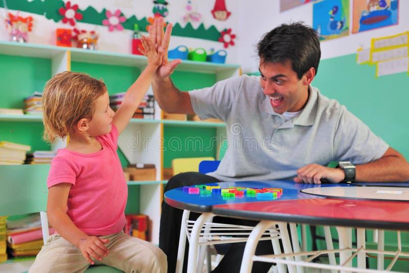 Donner préscolaire de professeur et d'enfant haut-cinq photographie stock