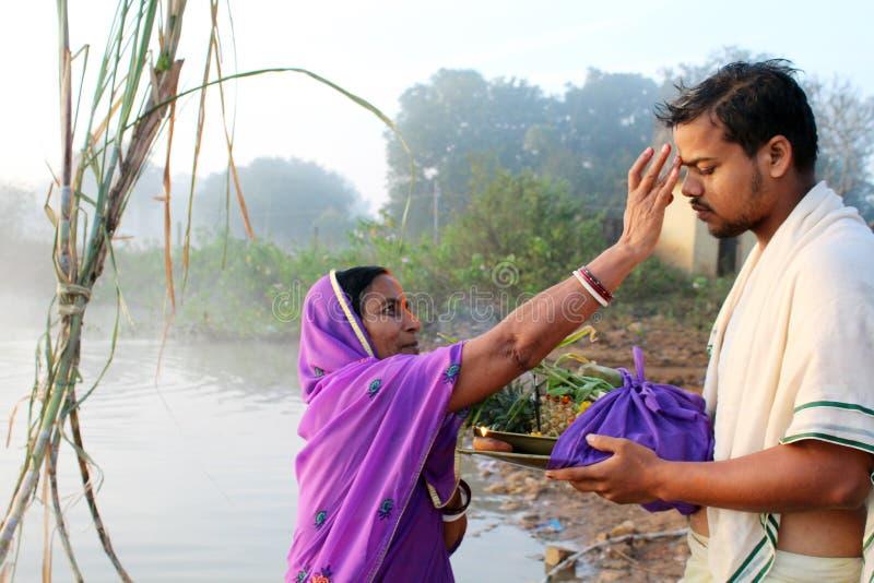 Donner Tilak au garçon par la mère chez Chhath Puja photos stock
