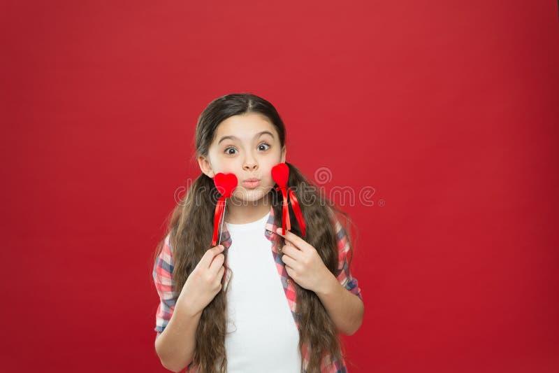 Donner un baiser d'air Petite fille drôle tenant des coeurs sur des bâtons Fille adorable avec de petits coeurs rouges Petit enfa photos stock