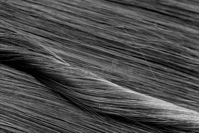 Donnez à la longue couleur une consistance rugueuse noire en gros plan de cheveux droits photos libres de droits