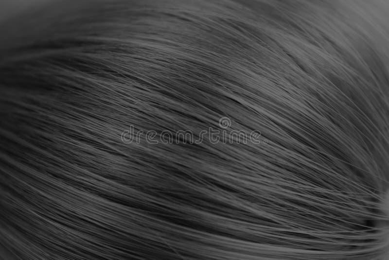 Donnez à la longue couleur une consistance rugueuse noire en gros plan de cheveux droits photographie stock libre de droits