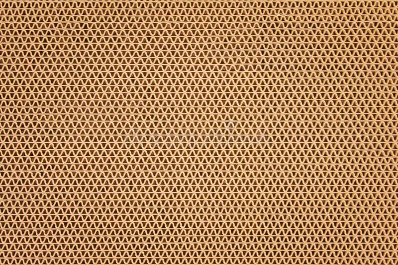 Donnez à la natte une consistance rugueuse en caoutchouc en plastique brune dans des modèles de forme d'ondulation sur le fond images stock