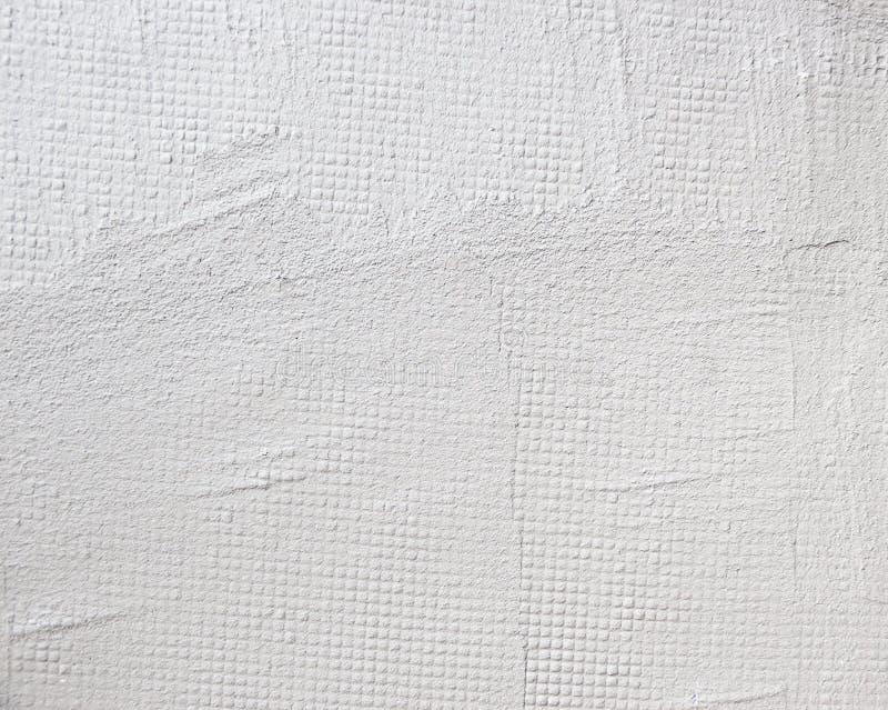 Donnez au mur une consistance rugueuse blanc stuccoed par fond avec le béton de maille photos stock
