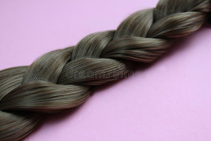 Donnez au plan rapproché une consistance rugueuse du fond gris de couleur de cheveux tressés photographie stock libre de droits