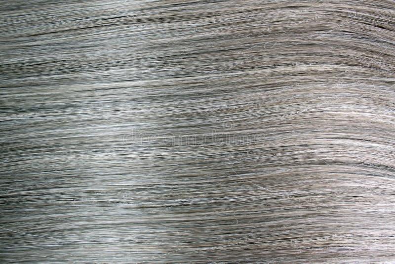 Donnez aux longs cheveux une consistance rugueuse droits en gros plan gris-clair image stock