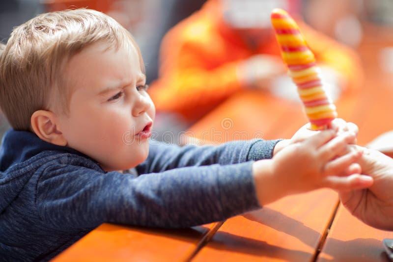 Donnez-moi cette glace ! Petit garçon obtenant une glace, extérieur au soleil à une table photo libre de droits