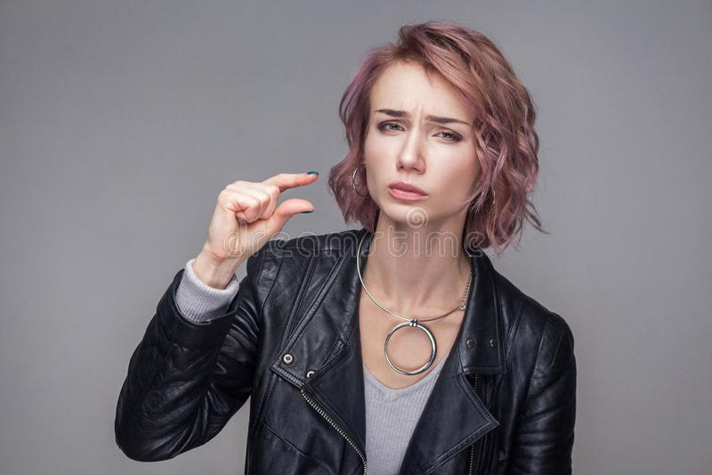 Donnez-moi un peu Portrait de belle fille pleine d'espoir avec les cheveux courts et de maquillage dans la position noire de vest photos stock