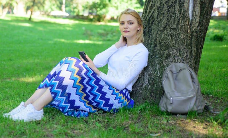 Donnez-vous la coupure et appréciez les loisirs La fille s'asseyent sur le maigre d'herbe sur le tronc d'arbre détendant à l'arri image libre de droits