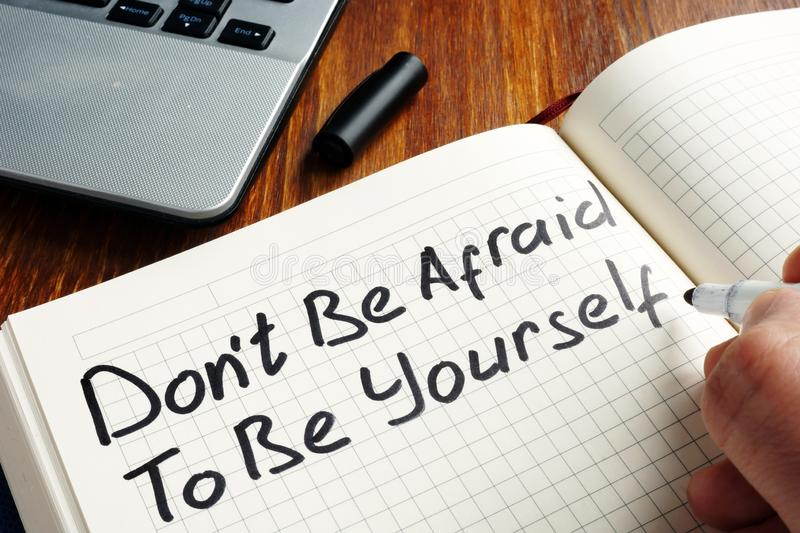 Dont be afraid to be yourself handwritten in a note. Motivation quote stock photos