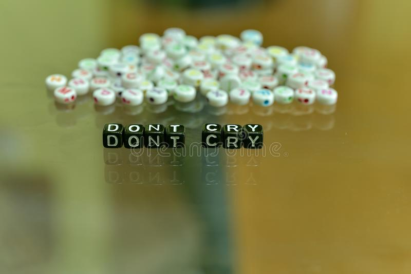 DONT CRY  written with Acrylic Black cube with white Alphabet Beads on the Glass Background.  royalty free stock image