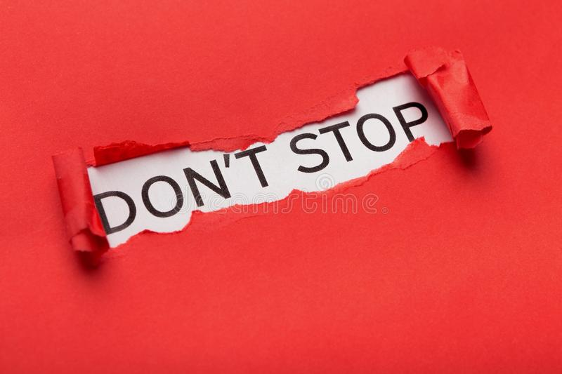 Dont stop phrase bursting out from torn red paper. Motivational poster with Dont spot phrase appearing behind torn red paper. Inspiration and support concept royalty free stock photos