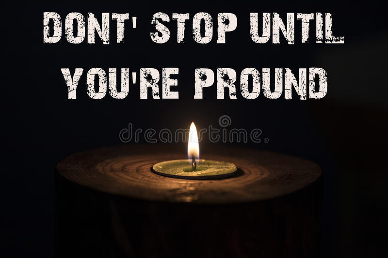 Dont` stop until you`re pround - white candle with dark backgrou stock images