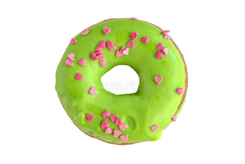 Donut bedeckt mit grüner Glasur und mit rosa Herzen besprüht stockbild