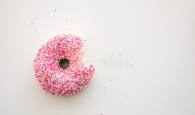 Doughnut with pink and white decoration isolated on white color background. Top view stock photos