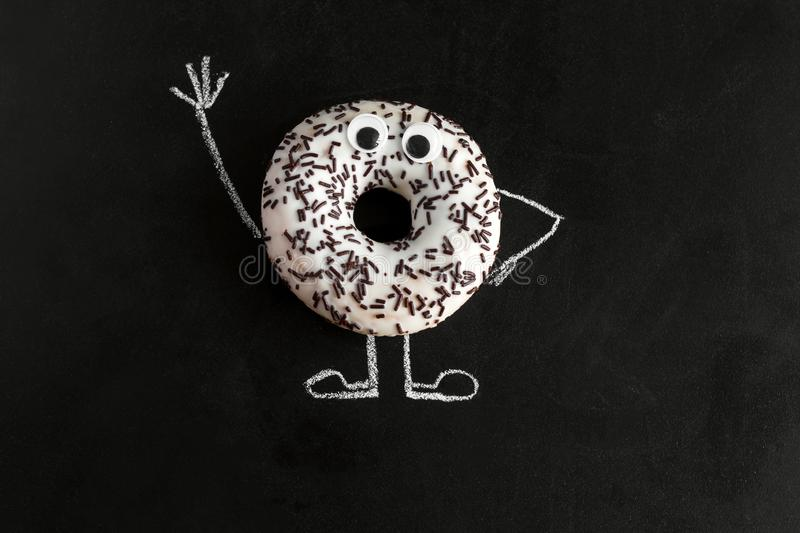 Donut on chalk board with chalk-drawn arms and legs and googly eyes. Top view donut on chalk board with chalk-drawn arms and legs and googly eyes stock images