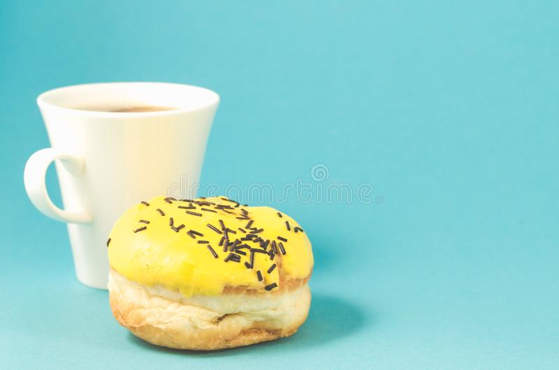 Donut and coffe cup on blue background/Donut in yellow glaze decorated with dark chocolate sticks and coffe cup isolated blue. Background. Copy space stock images