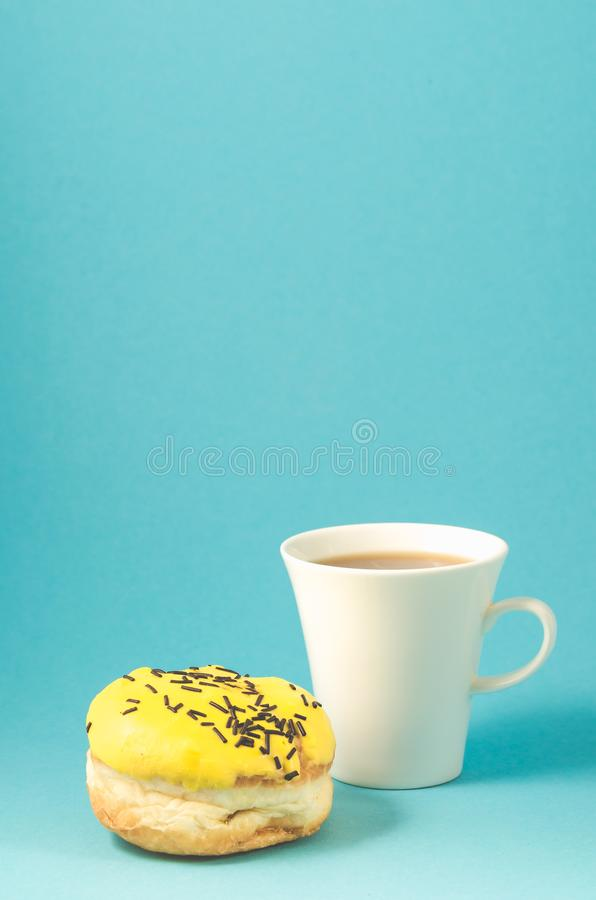 Donut and coffe cup on blue background/Donut in yellow glaze decorated with dark chocolate sticks and coffe cup isolated blue. Background stock images