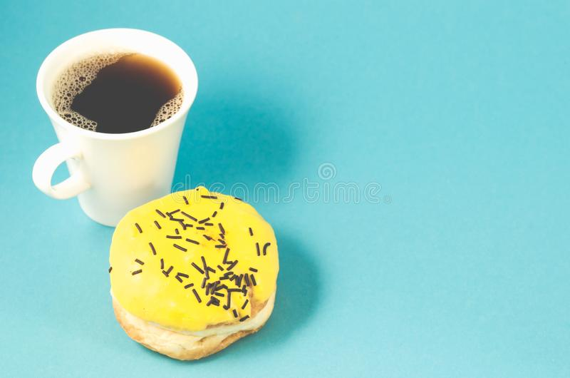 Donut and coffe cup on blue background/Donut in yellow glaze decorated with dark chocolate sticks and coffe cup isolated  blue. Background. Top view and copy royalty free stock image