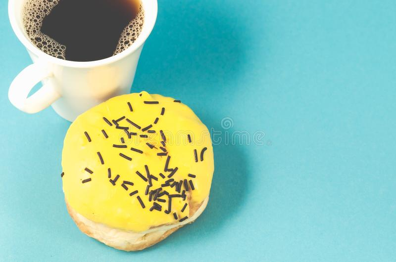 donut and coffe cup isolated on blue background /donut and coffe cup isolated on blue background. Top view and copy space stock photography