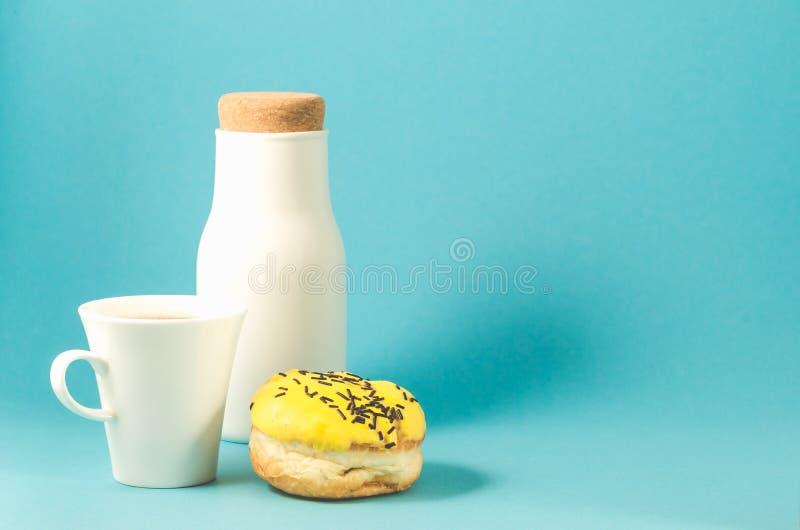 Donut in der gelben Glasur, in coffe Schale und in der Flasche auf blauem background/D lizenzfreies stockbild