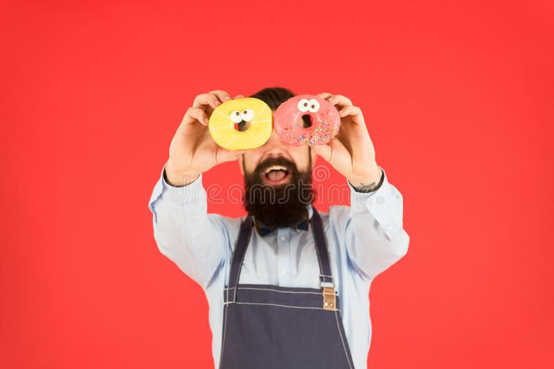 Donut food. Baked goods. Sweets and cakes. Junk food. Hipster bearded baker hold donuts. Eat donut. Cheerful mood royalty free stock photos