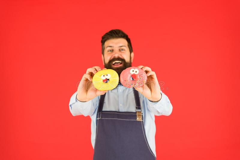Donut food. Baked goods. Sweets and cakes. Junk food. Hipster bearded baker hold donuts. Sweet donut. Waiter in cafe stock photo