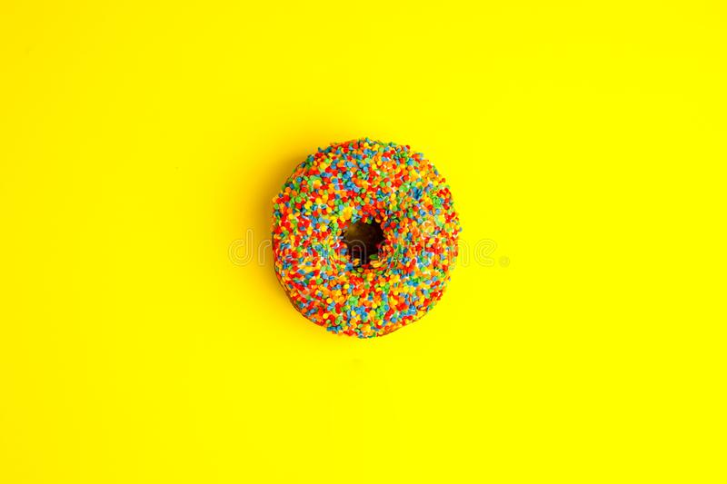 Donut glazed with sprinkles on a yellow background. Modern flat lay photo pattern in pop art style, party food. . royalty free stock photography