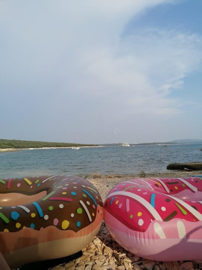 Donut gonfiabile sulla spiaggia fotografie stock libere da diritti
