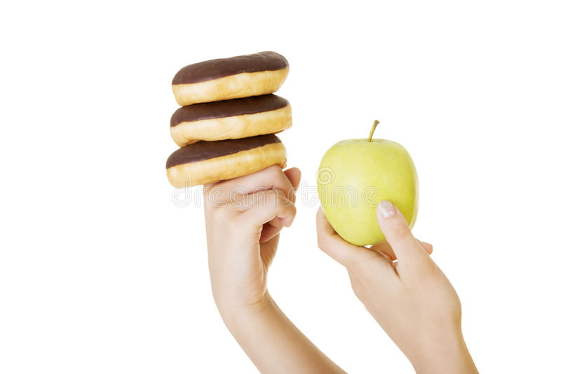 Donut or green apple - hard choice. stock images