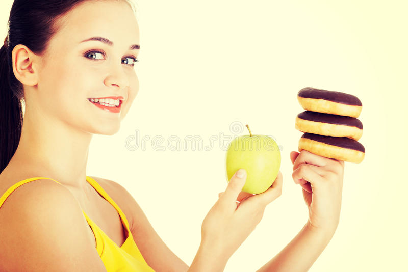 Donut or green apple - hard chose. stock image