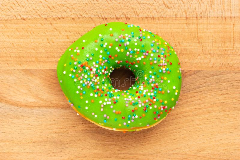 Donut green with sprinkles isolated on wooden background royalty free stock images